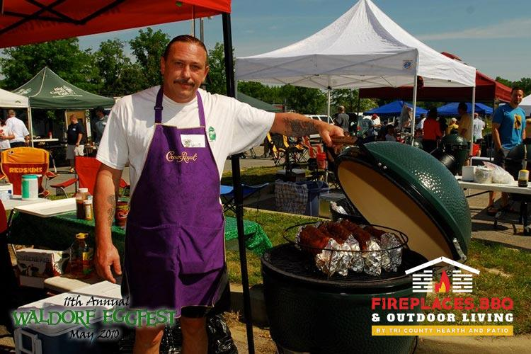 man in purple apron with big green egg