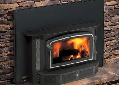 black fireplace insert on stone wall