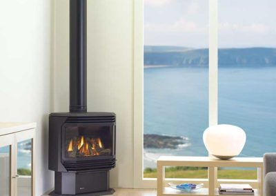 black stove with pipe by beach window