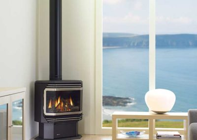 black stove with pipe next to beach window
